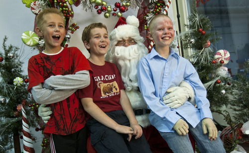 Chris Detrick  |  The Salt Lake Tribune Burn victims Spencer Cronin, 10, Kayden Godfrey, 8, and Tyler Bergman, 10, pose for a portrait with Santa during a fundraising event for the five young victims injured by a gasoline fire in Perry on Nov. 15 at The Peak in Perry Friday November 30, 2012. The boys, ages 7-10, were injured after they began experimenting with gasoline and fire while walking home from school. The combination resulted in an explosion that sent three of the boys by helicopter to the University of Utah Burn Center. The youngest victim, Tayton Winward, suffered burns over 14 percent of his body, mainly to his arms and face, and will remain in ICU for the next several weeks. Community members who would like to donate can do so for Tayton Windward at any Zions Bank branch or online under Kali Winward account #037 386419; or for Kayden Godfrey at any America First Credit Union branch under Blake Godfrey account #9056433.