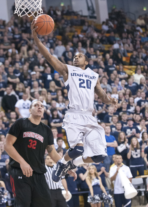 Utah State's Tenale Roland shoots past Western Oregon's Kolton Nelson during the first half of an NCAA college basketball game in Logan, Utah, Saturday, Dec. 8, 2012. (AP Photo/The Herald Journal, Jennifer Meyers)