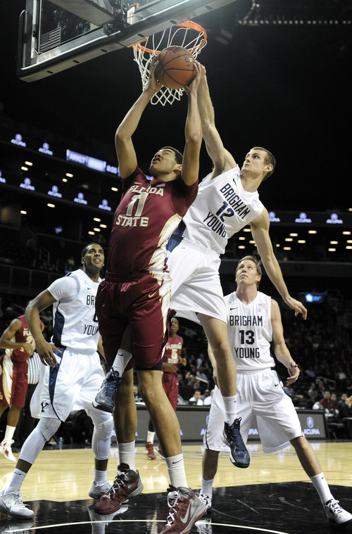 Florida State's Kiel Turpin (11) and Brigham Young's Josh Sharp (12) battle for a rebound in the first half of the Coaches vs. Cancer Classic basketball game on Friday, Nov., 16, 2012, at Barclays Center in New York. (AP Photo/Kathy Kmonicek)