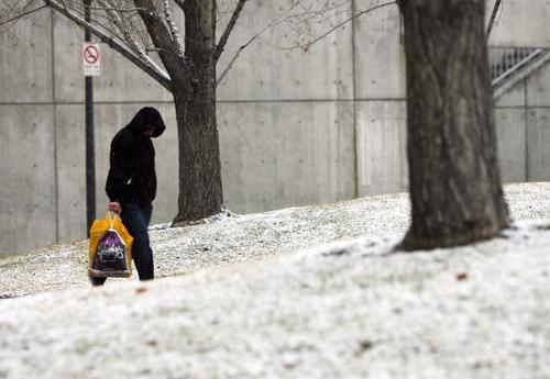 Kim Raff     The Salt Lake Tribune A man walks through  Library Square as snow lightly falls in Salt Lake City on December 8, 2012.