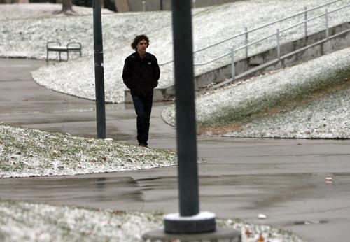 Kim Raff     The Salt Lake Tribune Mark Johnson walks through Library Square as snow lightly falls in Salt Lake City on December 8, 2012.