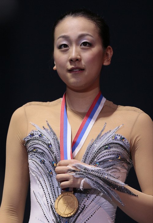 Asada Mao, of Japan, shows off her gold and medal during awarding ceremony at the ISU Figure Skating Grand Prix Final event, at Iceberg stadium in Sochi, Russia, on Saturday, Dec. 8, 2012. (AP Photo/Ivan Sekretarev)