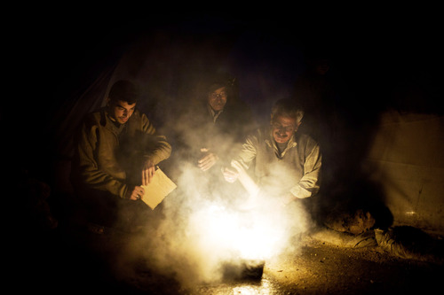 Syrian men heat a fire to boil water near their tent at a refugee camp near the Turkish border, in Azaz, Syria, Sunday, Dec. 9, 2012. (AP Photo/Manu Brabo)