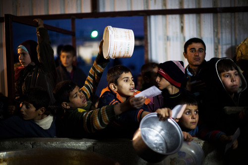 Manu Brabo  |  The Associated Press Syrian children wait in line for food distribution at a refugee camp near the Turkish border, in Azaz, Syria, Sunday, Dec. 9, 2012.
