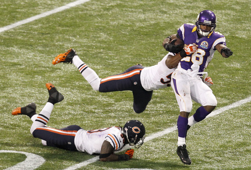 Minnesota Vikings running back Adrian Peterson, right, tries to break a tackle by Chicago Bears linebacker Nick Roach, center, and cornerback Charles Tillman, left, during the second half of an NFL football game Sunday, Dec. 9, 2012, in Minneapolis. (AP Photo/Genevieve Ross)