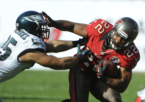 Tampa Bay Buccaneers running back Doug Martin (22) pushes off Philadelphia Eagles outside linebacker Mychal Kendricks (95) on a run during the second quarter of an NFL football game Sunday, Dec. 9, 2012, in Tampa, Fla. (AP Photo/Brian Blanco)