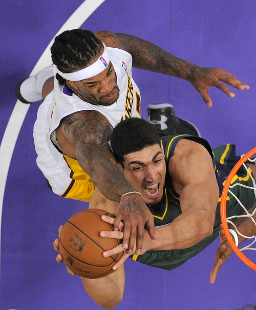 Utah Jazz center Enes Kanter, below, of Turkey, is fouled by Los Angeles Lakers center Jordan Hill during the first half of their NBA basketball game, Sunday, Dec. 9, 2012, in Los Angeles. (AP Photo/Mark J. Terrill)