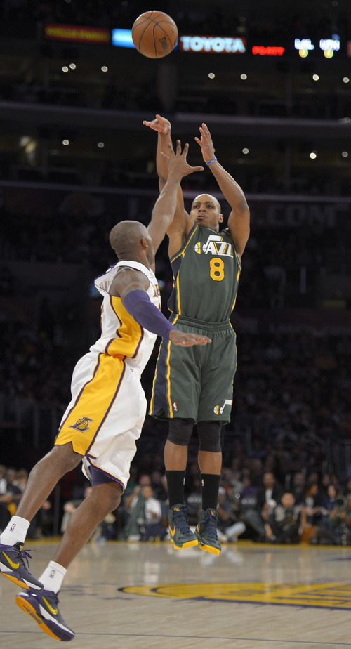 Utah Jazz's Randy Foye, right, shoots over Los Angeles Lakers guard Kobe Bryant during the first half of their NBA basketball game, Sunday, Dec. 9, 2012, in Los Angeles. (AP Photo/Mark J. Terrill)