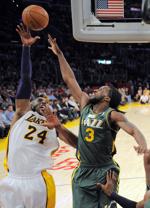 Los Angeles Lakers guard Kobe Bryant, left, puts up a shot as Utah Jazz forward DeMarre Carroll defends during the first half of their NBA basketball game, Sunday, Dec. 9, 2012, in Los Angeles. (AP Photo/Mark J. Terrill)