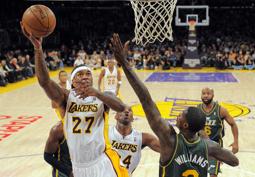 Los Angeles Lakers center Jordan Hill, left, puts p a shot as Utah Jazz forward Marvin Williams defends during the first half of their NBA basketball game, Sunday, Dec. 9, 2012, in Los Angeles. (AP Photo/Mark J. Terrill)
