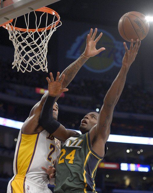 Utah Jazz forward Paul Millsap, right, shoots over Los Angeles Lakers center Jordan Hill during the first half of their NBA basketball game, Sunday, Dec. 9, 2012, in Los Angeles. (AP Photo/Mark J. Terrill)