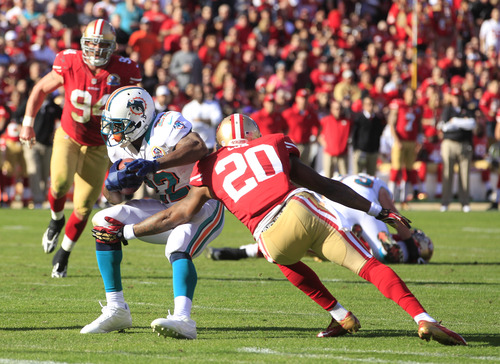 Miami Dolphins running back Reggie Bush is stopped with the ball by San Francisco 49ers defensive back Perrish Cox (20) during the first quarter of an NFL football game in San Francisco, Sunday, Dec. 9, 2012. At left is San Francisco 49ers defensive end Justin Smith (94). (AP Photo/Ben Margot)