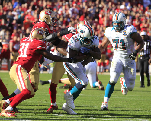 Miami Dolphins running back Reggie Bush carries the ball past San Francisco 49ers strong safety Donte Whitner (31) during the first quarter of an NFL football game in San Francisco, Sunday, Dec. 9, 2012. At right is Miami Dolphins tackle Jonathan Martin (71). (AP Photo/Ben Margot)