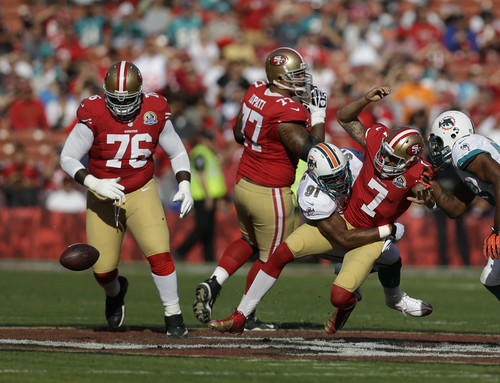 San Francisco 49ers quarterback Colin Kaepernick (7) is hit by Miami Dolphins defensive end Cameron Wake (91) after losing control of the ball during the first quarter of an NFL football game in San Francisco, Sunday, Dec. 9, 2012. Looking on is San Francisco 49ers tackle Anthony Davis (76) and guard Mike Iupati (77). (AP Photo/Marcio Jose Sanchez)