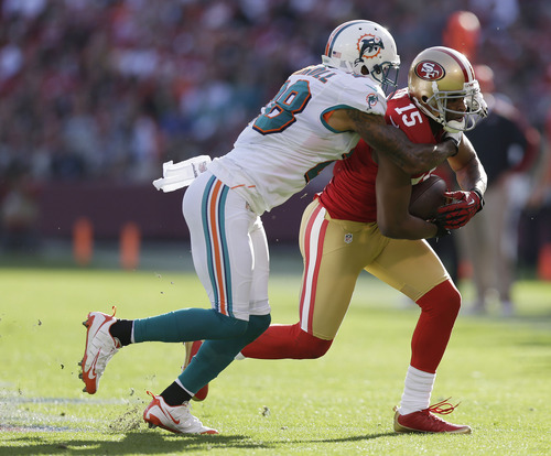 San Francisco 49ers wide receiver Michael Crabtree, right, runs with the ball before being stopped by Miami Dolphins cornerback Nolan Carroll, left, during the first quarter of an NFL football game in San Francisco, Sunday, Dec. 9, 2012. (AP Photo/Marcio Jose Sanchez)