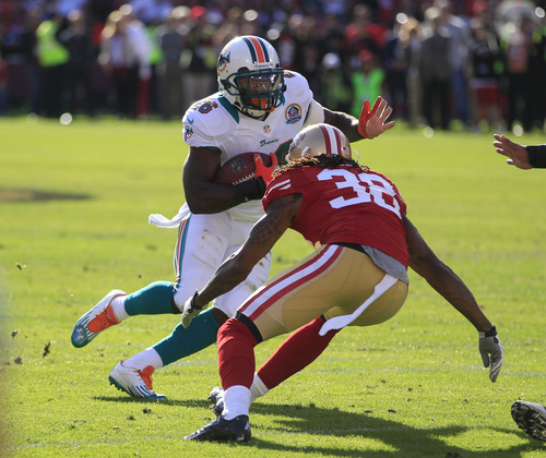 Miami Dolphins running back Lamar Miller carries the ball as San Francisco 49ers free safety Dashon Goldson looks on during the first quarter of an NFL football game in San Francisco, Sunday, Dec. 9, 2012. (AP Photo/Ben Margot)