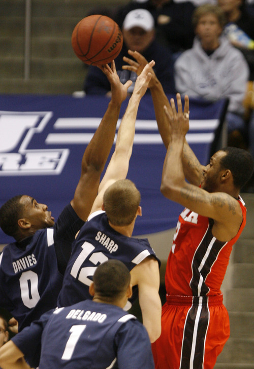 Rick Egan  | The Salt Lake Tribune   Brigham Young Cougars forward Brandon Davies (0) blocks a shot by Utah Utes guard/forward Aaron Dotson (2) in basketball action between the Brigham Young Cougars and the Utah Utes at the Marriott Center in Provo, Saturday, December 8, 2012.