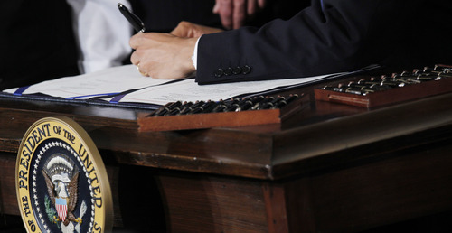 FILE - This March 23, 2010 file photo shows Ttwenty two pens next to President Barack Obama as he signs the health care reform bill in the East Room of the White House in Washington. Your medical plan is  facing an unexpected expense, so you probably are, too. It's a new, $63-per-head fee to cushion the cost of covering people with pre-existing conditions under President Barack Obama's health overhaul. The charge, buried in a recent regulation, works out to tens of millions of dollars for the largest company health plans, and much of that is likely to be passed on to employees. Multiple pens are used to sign legislation, and then distributed to supporters of the legislation. (AP Photo/Charles Dharapak, File)