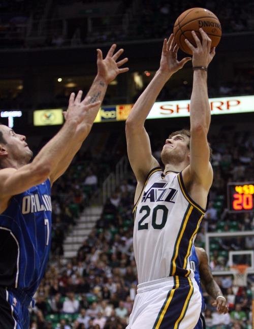 Kim Raff  |  The Salt Lake Tribune (right) Utah Jazz shooting guard Gordon Hayward (20) catches a pass over the hands of (left) Orlando Magic shooting guard J.J. Redick (7) during a game at EnergySolutions Arena in Salt Lake City on December 5, 2012. Jazz went on to win 87-81.