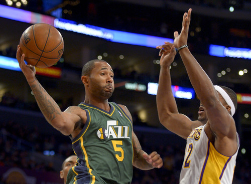 Utah Jazz guard Mo Williams, left, passes around Los Angeles Lakers center Dwight Howard during the first half of their NBA basketball game, Sunday, Dec. 9, 2012, in Los Angeles. (AP Photo/Mark J. Terrill)