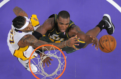 Utah Jazz forward Paul Millsap, right, puts up a shot as Los Angeles Lakers center Jordan Hill defends during the first half of their NBA basketball game, Sunday, Dec. 9, 2012, in Los Angeles. (AP Photo/Mark J. Terrill)