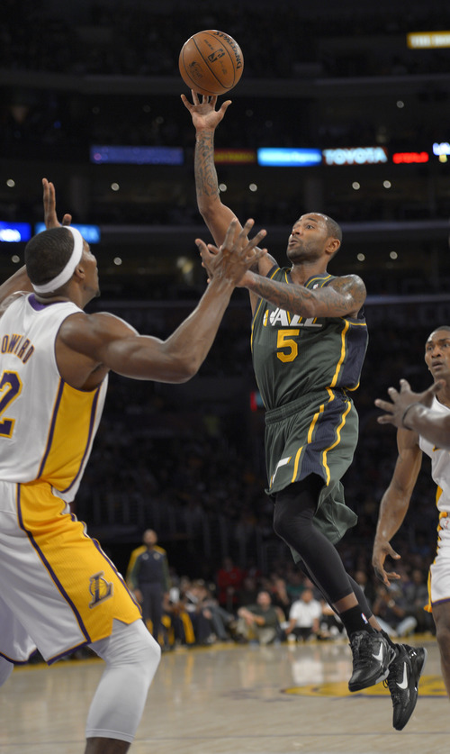 Utah Jazz guard Mo Williams, right, shoots over Los Angeles Lakers center Dwight Howard during the first half of their NBA basketball game, Sunday, Dec. 9, 2012, in Los Angeles. (AP Photo/Mark J. Terrill)