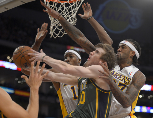 Utah Jazz guard Gordon Hayward, middle, drives to the basket between Los Angeles Lakers' Dwight Howard, left, and Jordan Hill during the first half of their NBA basketball game, Sunday, Dec. 9, 2012, in Los Angeles. (AP Photo/Mark J. Terrill)