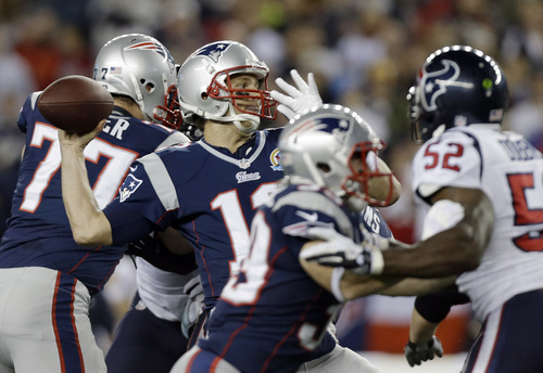 New England Patriots quarterback Tom Brady (12) passes over Houston Texans inside linebacker Tim Dobbins (52) during the first quarter of an NFL football game in Foxborough, Mass., Monday, Dec. 10, 2012. (AP Photo/Elise Amendola)