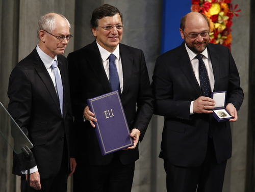 """From left, European Council President Herman Van Rompuy, European Commission President Jose Manuel Barroso and European Parliament President Martin Schulz with the Nobel diploma on the podium at the City Hall, Oslo, during the Nobel Peace Prize ceremony, Monday Dec. 10, 2012. The European Union has received this year's Nobel Peace Prize in the Norwegian capital, for promoting """"peace and reconciliation, democracy and human rights"""" in Europe for six decades following the tremendous devastation of World War II. (AP Photo/Heiko Junge/NTB Scanpix, Pool)"""