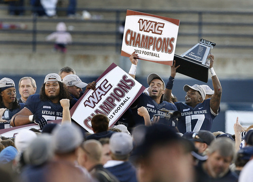 Scott Sommerdorf  |  The Salt Lake Tribune               Utah State Aggies CB Will Davis (17), right, hoists the WAC trophy as his team mate WR Matt Austin holds aloft a WAC Champions sign after the win over Idaho. Utah State defeated Idaho 45-9 in Logan, Saturday, November 24, 2012 to become champions of the WAC.