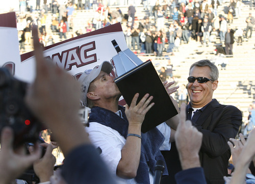 Scott Sommerdorf  |  The Salt Lake Tribune               Utah State head coach Gary Andersen kisses the WAC trophy as Athletic Director Scott Barnes applaudes at right. Utah State defeated Idaho 45-9 in Logan, Saturday, November 24, 2012 to become champions of the WAC.