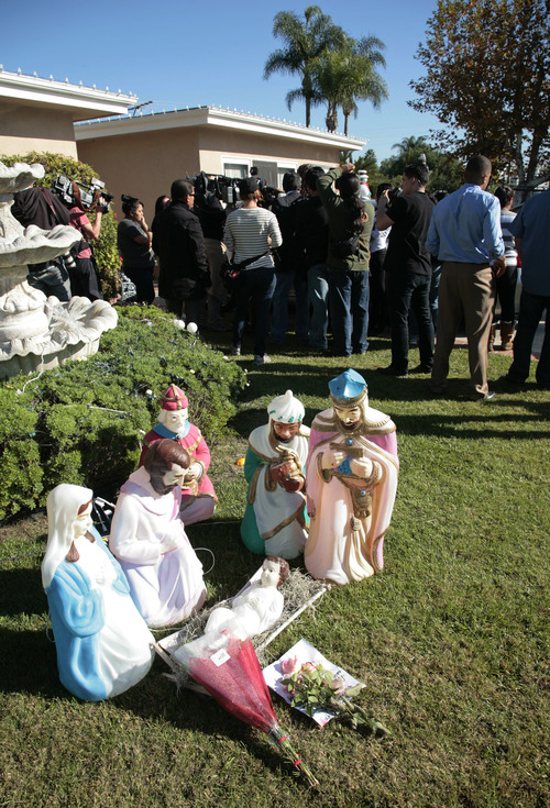 Flowers lie in front of a nativity scene as media gather outside the home of Jenni Rivera's mother in Lakewood, Calif. Monday, Dec. 10, 2012. Rivera died Sunday in a plane crash in Mexico. (AP Photo/Jason Redmond)