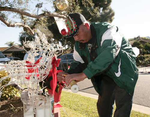 Fan Jose Ruelas lights a candle outside the home of singer Jenni Rivera's mother in Lakewood, Calif. Monday, Dec. 10, 2012. Rivera died Sunday in a plane crash in Mexico. (AP Photo/Jason Redmond)