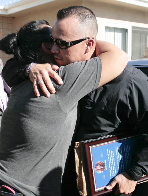 Pedro Rivera, Jr., right, brother of singer Jenni Rivera, is greeted by a well wisher as he arrives at his mother's home in Lakewood, Calif. Monday, Dec. 10, 2012. Jenni Rivera died Sunday in a plane crash in Mexico. (AP Photo/Jason Redmond)
