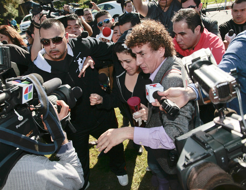 Jacqueline Rivera, center, daughter of singer Jenni Rivera, is swarmed by media as she arrives at her grandmother's home in Lakewood, Calif. Monday, Dec. 10, 2012. Jenni Rivera died Sunday in a plane crash in Mexico. (AP Photo/Jason Redmond)
