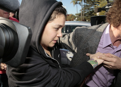 Jacqueline Rivera, daughter of singer Jenni Rivera, is swarmed by media as she arrives at her grandmother's home in Lakewood, Calif. Monday, Dec. 10, 2012. Jenni Rivera died Sunday in a plane crash in Mexico. (AP Photo/Jason Redmond)