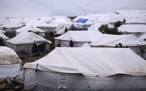 In this Monday, Dec. 10, 2012 photo, Syrians who fled their homes stand by their tents at a camp for displaced Syrians, in the village of Atmeh, Syria. This tent camp sheltering some of the hundreds of thousands of Syrians uprooted by the country's brutal civil war has lost the race against winter: the ground under white tents is soaked in mud, rain water seeps into thin mattresses and volunteer doctors routinely run out of medicine for coughing, runny-nosed children. (AP Photo/Muhammed Muheisen)