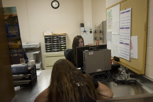 Kim Raff | The Salt Lake Tribune (right) Pretrial jail screener Kellie Madsen checks the background of a woman who was recently brought into the Salt Lake County Jail to see if she qualifies for pretrial release.