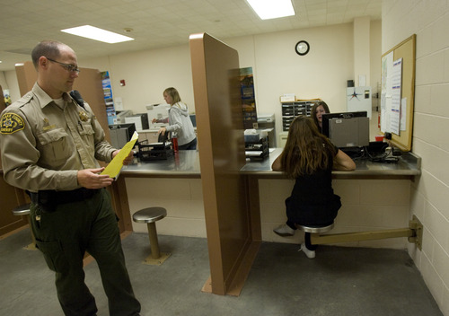 Kim Raff | The Salt Lake Tribune (left) Officer Schuyler Pack grabs paperwork as pretrial jail screener (right) Kellie Madsen checks the background of a woman who was recently brought into the Salt Lake County Jail to see if she qualifies for pretrial release.