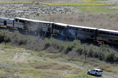 Emergency crews work around two cars  at the site of a deadly collision between an Amtrak westbound train and a truck on  U.S. 95 about 4 miles south of Interstate 80 on Friday, June 24, 2011, 70 miles east of Reno, Nev. (AP Photo/The Reno Gazette-Journal, Marilyn Newton)