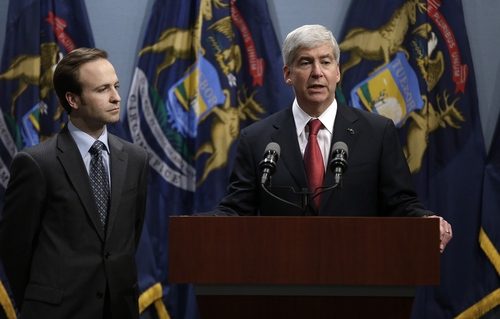 Gov. Rick Snyder, right, speaks as Lt. Gov. Brian Calley listens at a news conference in Lansing, Mich., Tuesday, Dec. 11, 2012. Michigan became the 24th state with a right-to-work law after Snyder signed the bill Tuesday. (AP Photo/Paul Sancya)