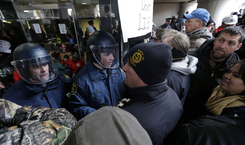 Michigan State Police push protesters away from the entrance of the George W. Romney State Building, where Gov. Snyder has an office in Lansing, Mich., Tuesday, Dec. 11, 2012. The crowd is protesting right-to-work legislation passed last week. Michigan could become the 24th state with a right-to-work law next week. Rules required a five-day wait before the House and Senate vote on each other's bills; lawmakers are scheduled to reconvene Tuesday and Gov. Snyder has pledged to sign the bills into law. (AP Photo/Paul Sancya)