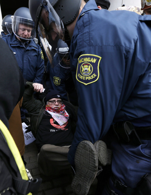 Michigan State Police carry a protester from a rally at the George W. Romney State Building, where Gov. Snyder has an office in Lansing, Mich., Tuesday, Dec. 11, 2012. The crowd is protesting right-to-work legislation passed last week. Michigan could become the 24th state with a right-to-work law next week. Rules required a five-day wait before the House and Senate vote on each other's bills; lawmakers are scheduled to reconvene Tuesday and Gov. Snyder has pledged to sign the bills into law. (AP Photo/Paul Sancya)