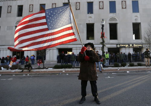 Protester Paula Merwin, of Leslie, Mich., stands with an American flag outside the George W. Romney State Building, where Gov. Snyder has an office in Lansing, Mich., Tuesday, Dec. 11, 2012. The crowd is protesting right-to-work legislation passed last week. Michigan could become the 24th state with a right-to-work law next week. Rules required a five-day wait before the House and Senate vote on each other's bills; lawmakers are scheduled to reconvene Tuesday and Gov. Snyder has pledged to sign the bills into law. (AP Photo/Paul Sancya)