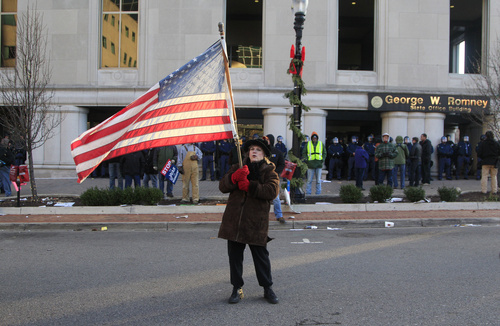 Paula Merwin of Leslie, Mich., waves an American flag outside the George W. Romney State Office Building as lawmakers push final versions of right-to-work legislation in Lansing, Mich., Tuesday, Dec. 11, 2012. The GOP majority has used its superior numbers and backing from Gov. Rick Snyder to speed the legislation through the House and Senate last week, brushing aside denunciations and walkouts by helpless Democrats and cries of outrage from union activists who swarmed the state Capitol hallways and grounds. (AP Photo/Carlos Osorio)