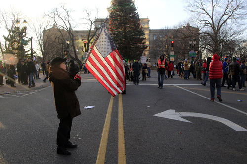 Paula Merwin of Leslie, Mich., waves an American flag outside the state Capitol as lawmakers push final versions of right-to-work legislation in Lansing, Mich., Tuesday, Dec. 11, 2012. The GOP majority has used its superior numbers and backing from Gov. Rick Snyder to speed the legislation through the House and Senate last week, brushing aside denunciations and walkouts by helpless Democrats and cries of outrage from union activists who swarmed the state Capitol hallways and grounds. (AP Photo/Carlos Osorio)