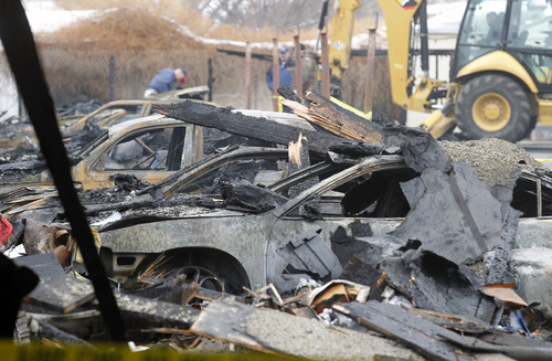 Al Hartmann  |  The Salt Lake Tribune West Valley City Fire Department investigators sift through debris of 10 cars that burned in a carport at apartment complex at 3685 S. 2200 West on Dec. 11.  The fire started about 12:30 a.m.