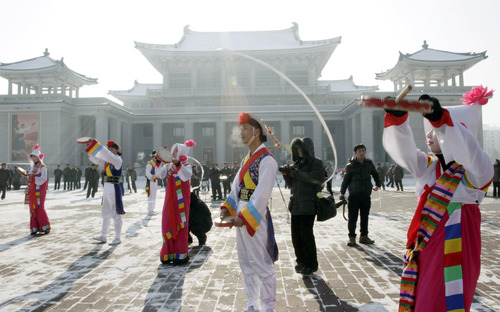 North Korean youths in traditional Korean outfit play instruments in front of the Pyongyang Grand Theatre in Pyongyang, North Korea, to celebrate a rocket launch on Wednesday, Dec. 12, 2012. North Korea appeared to successfully fire a long-range rocket Wednesday, defying international warnings as the regime of Kim Jong Un pushes forward with its quest to develop the technology needed to deliver a nuclear warhead. (AP Photo/Jon Chol Jin)