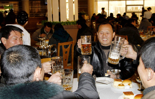 North Koreans toast after hearing the news of a  rocket launch with beer at the newly-built Mansukyo Restaurant on Wednesday, Dec. 12, 2012 in Pyongyang, North Korea. North Korea appeared to successfully fire a long-range rocket Wednesday, defying international warnings as the regime of Kim Jong Un pushes forward with its quest to develop the technology needed to deliver a nuclear warhead. (AP Photo/Kim Kwang Hyon)