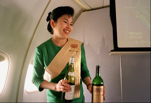 """FILE - In this Dec. 14, 1996, file photo, a Thai Airways International airline flight attendant offers a passenger a selection of wine during a flight from Singapore to Bangkok. Airlines have found a way to take the edge off the stress of flying and make a few extra bucks along the way: fancy new cocktails, craft beers and elegant wines. In December 2012 Virgin America will launch its """"send a drink"""" feature where one passenger can use the plane's seatback entertainment system to buy another passenger a beverage. (AP Photo/Richard Vogel)"""